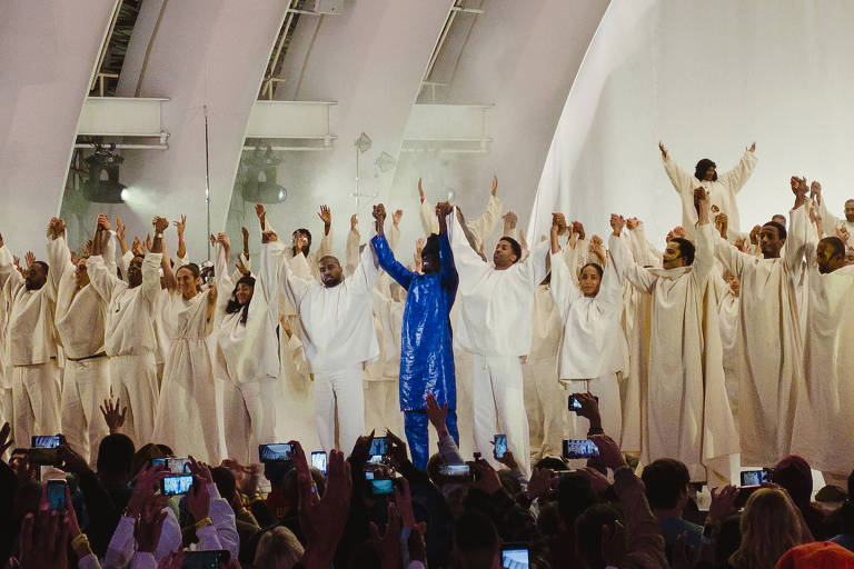 pessoas com as mãos levantadas em cima de palco