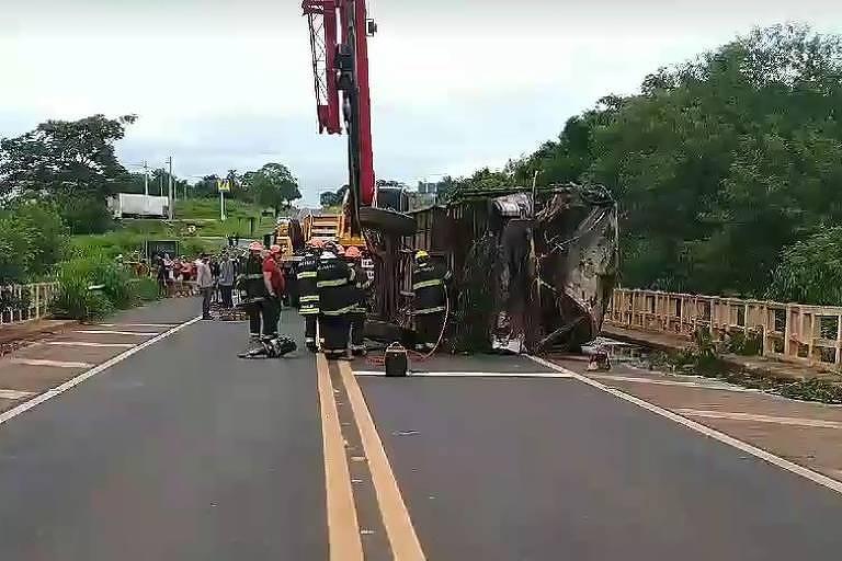 Equipes de resgate estão posicionadas ao lado de ônibus tombado numa estrada. ao fundo há um guincho