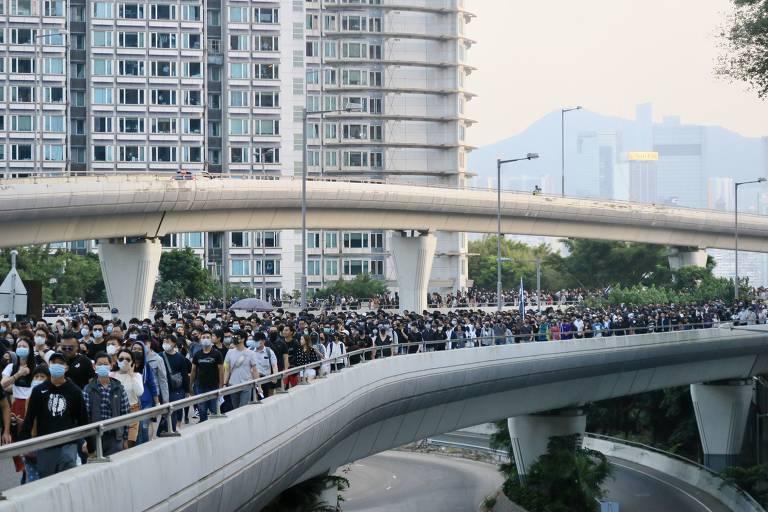 Multidão de manifestantes vestidos de preto e branco atravessa ponte