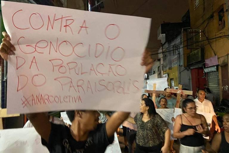 Moradores da favela Paraisópolis, protestam usando cartazes contra a ação da PM durante o baile Funk na madrugada deste domingo(1)