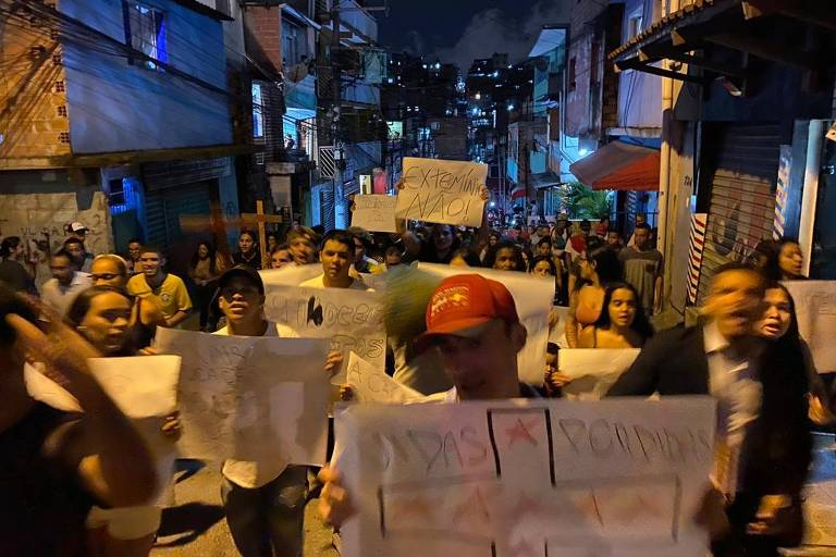 Moradores da favela Paraisópolis protestam usando cartazes contra a ação da PM durante o baile funk na madrugada deste domingo (1)