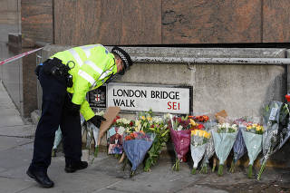 A police officer places a floral tribute near the scene of a stabbing on London Bridge, in London