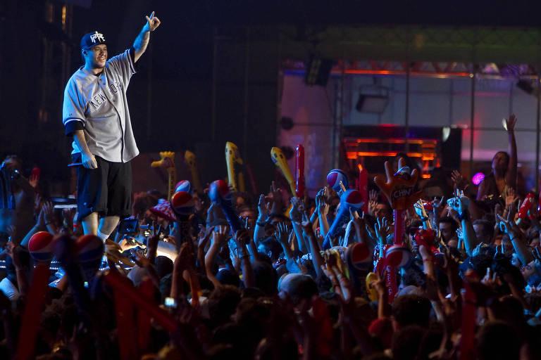 cantor com braço levantado durante show