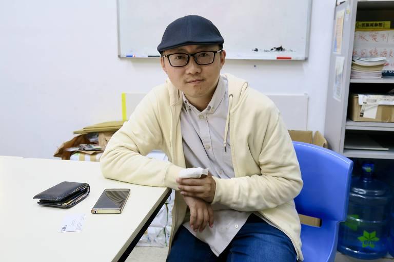 De boina azul, o conselheiro eleito Stanley Ho está sentado de frente para uma mesa de escritório. Ele tem um dos dedos indicadores engessado