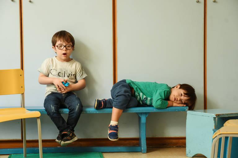 Dois meninos, um deles com sentado e outro deitado, estão sobre um banco azul