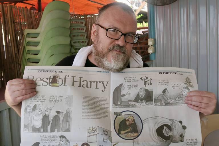 Homem branco, calvo e de barba branca segura jornal impresso aberto, mostrando suas charges