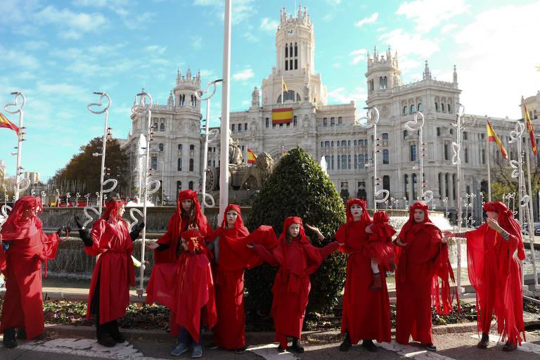Manifestantes cobertos com roupas vermelhas diante da fonte de Cibeles