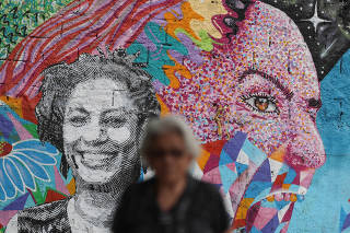 A woman walks past a wall with an image of murdered activist and councilwoman Marielle Franco, in Rio de Janeiro