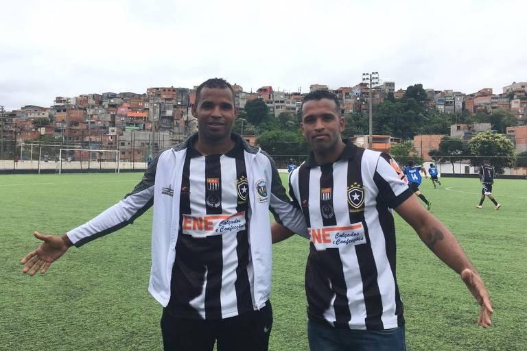 Diego Lima (esq.) e Ronaldo Souza, em frente ao campo do Botafogo de Guaianases, com o morro da favela ao fundo