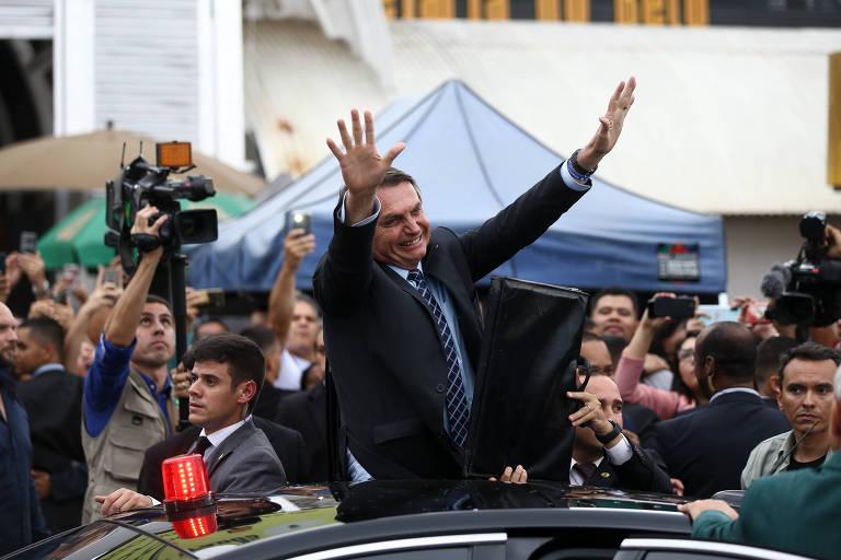 O presidente Bolsonaro acena para apoiadores ao chegar a feira popular em Brasília