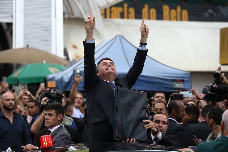 de terno, bolsonaro ergue os braços e olha para o céu, e tem muitas pessoas em volta