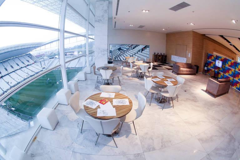 Sala com mesas e cadeiras e vista para gramado