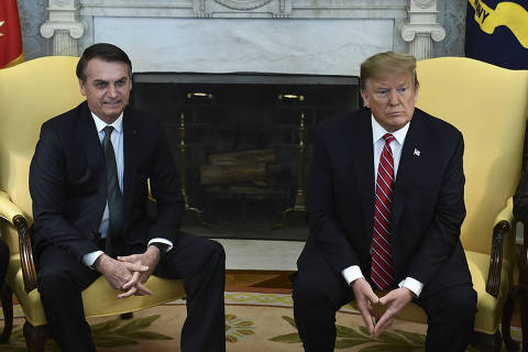(FILES) In this file photo taken on March 19, 2019 US President Donald Trump(R)and Brazilian President Jair Bolsonaro meet in the Oval Office at the White House in Washington,DC. - President Donald Trump struck back on December 2, 2019 at what he called unfair policies by Brazil and Argentina, saying he is reinstating tariffs on steel and aluminum from those countries.
