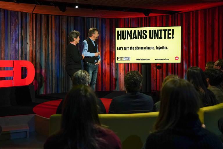 """Dois dos participantes da iniciativa em frente a telão onde se lê: """"Humanos, uni-vos"""""""