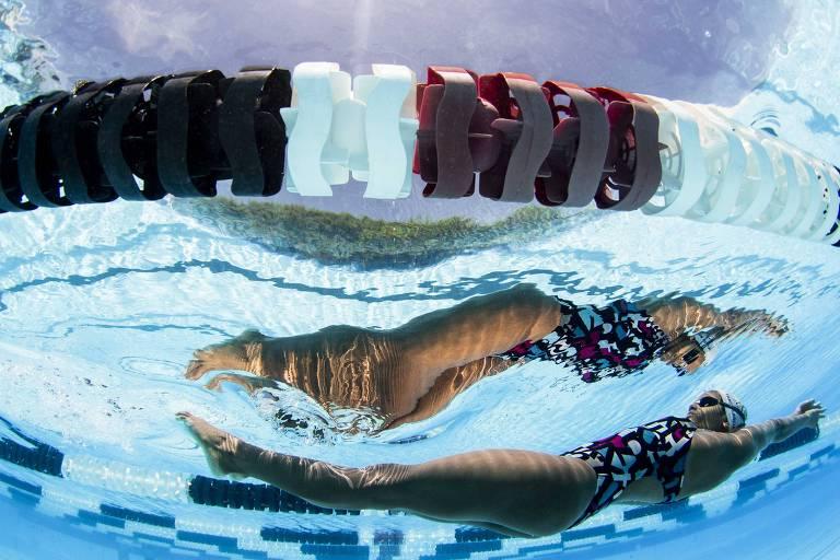 A foto foi tirada debaixo da água, a nadadora está totalmente submersa, de costas, com os braços esticados. É possível ver seu reflexo na superfície da piscina azul