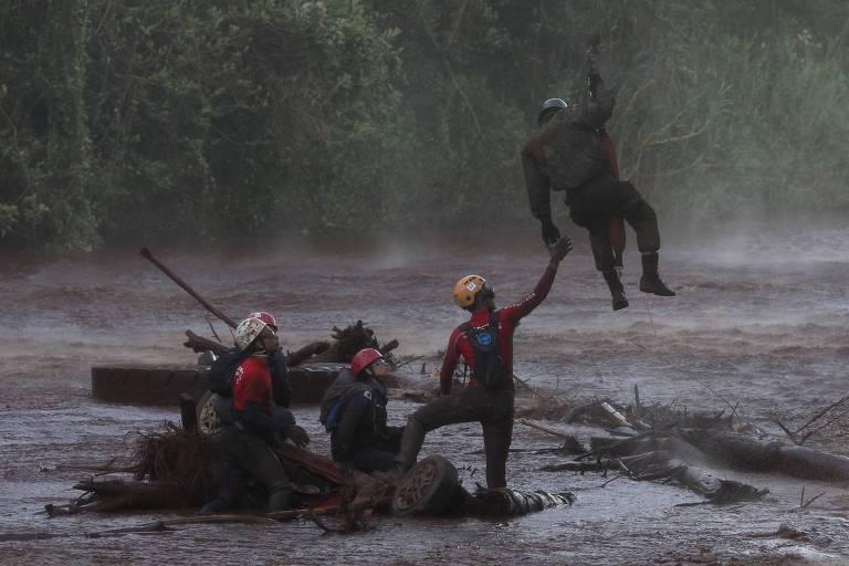Três homens de capacetes e camisetas vermelhas estão ilhados em um rio de lama, eles esperam o resgate sentados em entulhos. Ao mesmo tempo, um outro homem, em pé, estica o braço para um militar que está suspenso por um cabo, provavelmente trazido por um helicoptero, para regastá-los