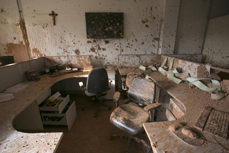 Escritório com bancadas de computador, cadeira e televisão na parede, todo sujo de lama