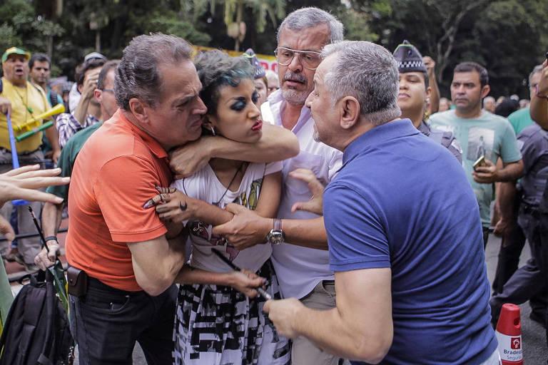 Três homens brancos de cabelos grisalhos cercam uma mulher. Um deles a agarra por trás e segura pelo pescoço, enquanto outro gesticula agressivamente em sua direção. O terceiro homem, de camisa rosa e óculos, a seguras pelos braços. A mulher usa batom vermelho e sombra azul nos olhos, sua feição é de profunda raiva