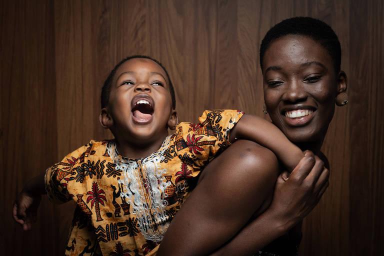 A mãe está de lado e olha para a câmera sorrindo largo; o bebê está vestido com trajes amarelos e pretos, típicos da Guiné Bissau, e sorri olhando para cima, pendurado em sua mãe pelas costas