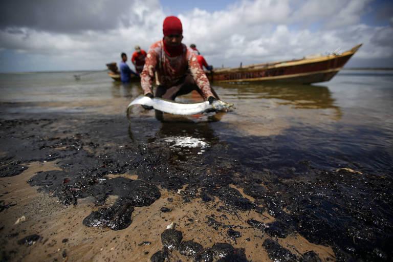 Na beira do mar, pescador se ajoelha e segura uma moreia cumprida em suas mãos. Ele está cercado de óleo negro que chega na praia.