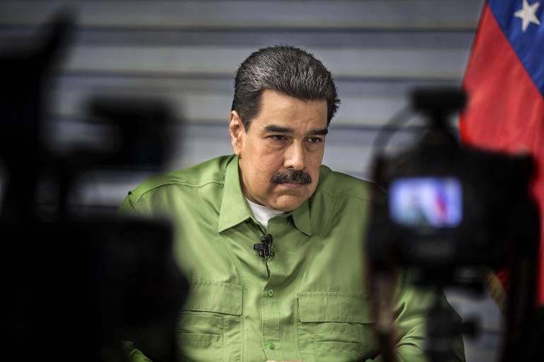 De bigodes espessos e camisa verde limão, Nicolás Maduro se senta diante das câmeras, ao lado de uma bandeira vermelha com estrelas brancas da Venezuela