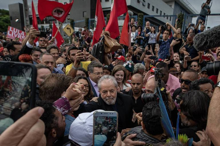 Lula, vestido de preto, está totalmente cercado por uma multidão de pessoas, militantes, políticos e apoiadores. Bandeiras vermelhas são balançadas ao fundo.