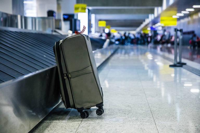 Mala de mão ao lado de esteira de bagagens no aeroporto de Guarulhos