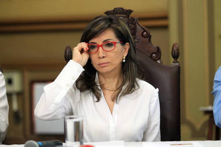 Ex-prefeita de Ribeirão Preto, Dárcy Vera, está sentada com o semblante sério e a mão direita nos óculos.