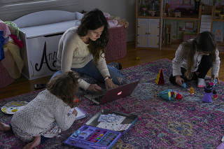Caitlin Houston, an Instagram influencer, works while her daughters play at home in Connecticut, Nov. 25, 2019. (Yael Malka/The New York Times)
