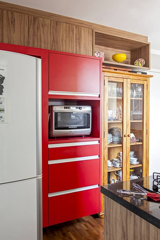 Fã de cores fortes, a arquiteta Cristiane Schiavoni desenhou o armário que mescla porta alta tipo basculante, nicho para o micro-ondas, gaveta e gavetões – execução da Marcenaria Decorcity. Ao lado, o louceiro de madeira com portas de vidro foi comprado pronto na Tok&Stok