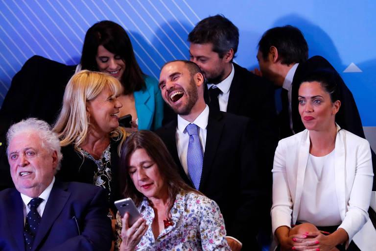 O indicado para comandar a economia, Martín Guzmán (centro, de gravata azul), dá risada durante o anúncio do gabinete ao lado de seus colegas