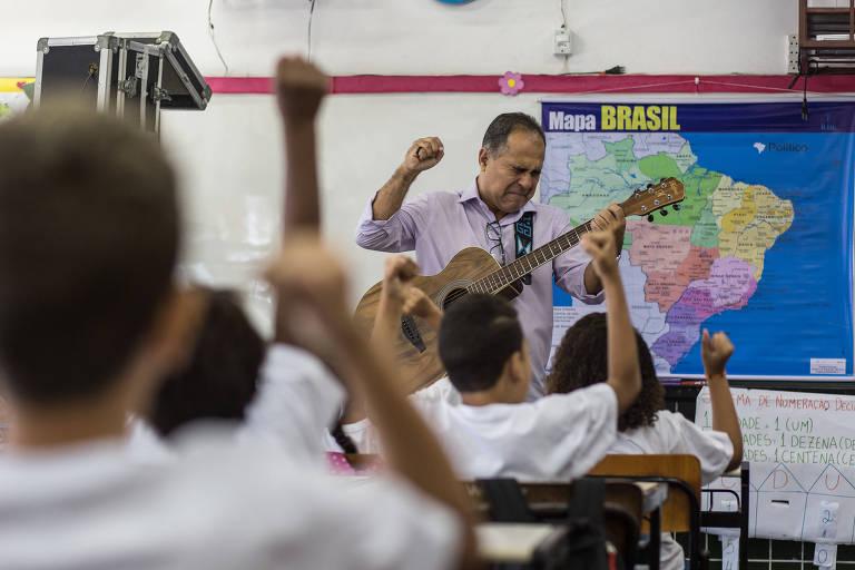 O professor, Roberto de Oliveira Ferreira, 56, toca violão para entreter os alunos