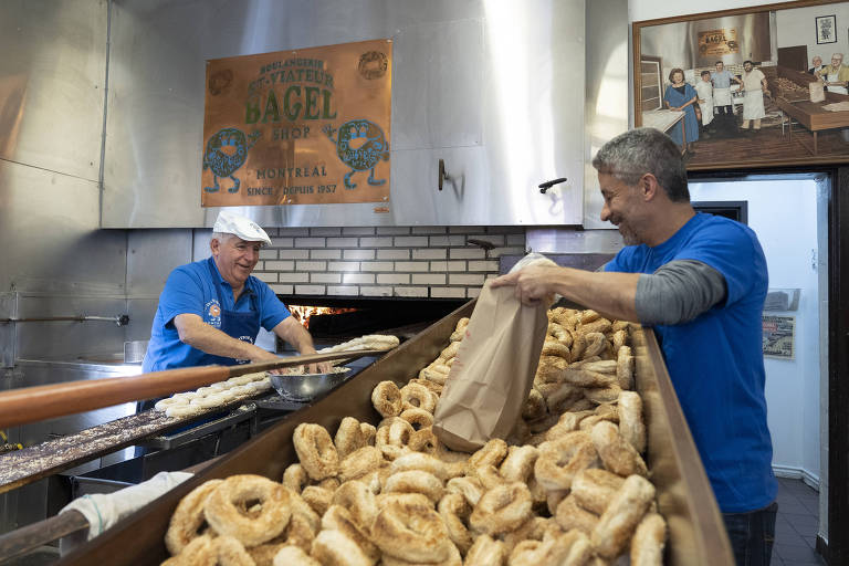 Joe Morena, left, the owner of St-Viateur Bagel, prepares a batch of bagels in a wood-burning oven in Montreal, Quebec, Canada on Nov. 8, 2019. A culinary symbol of Montreal has become ensnared in a battle pitting environmentalists who want to abolish the pollutant-producing ovens against bagel-loving traditionalists. (Chris Wattie/The New York Times)