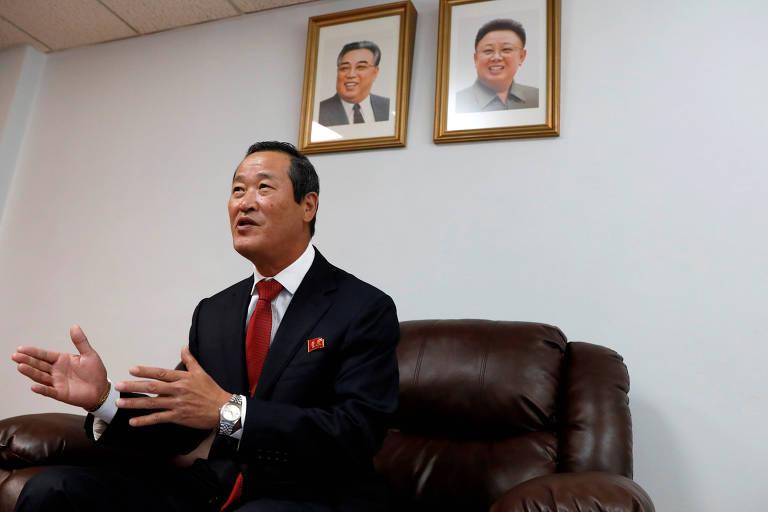homem fala sentado em sofá, com fotos de líderes norte-coreanos mortos atrás, na parede