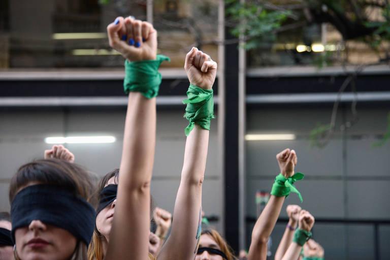 punhos erguidos de mulheres com lenços verdes amarrados