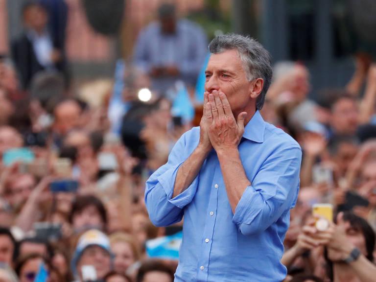 Na foto, o ex-presidente da Argentina, Mauricio Macri, aparece em primeiro plano, vestindo uma camiseta azul clara e com as duas mãos na boca. Ao fundo, diversos de seus apoiadores podem ser vistos.