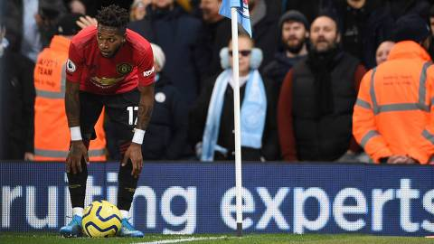 Manchester United's Brazilian midfielder Fred (L) tries to take a penalty after being pelted with objects from the crowd during the English Premier League football match between Manchester City and Manchester United at the Etihad Stadium in Manchester, north west England, on December 7, 2019. (Photo by Oli SCARFF / AFP) / RESTRICTED TO EDITORIAL USE. No use with unauthorized audio, video, data, fixture lists, club/league logos or 'live' services. Online in-match use limited to 120 images. An additional 40 images may be used in extra time. No video emulation. Social media in-match use limited to 120 images. An additional 40 images may be used in extra time. No use in betting publications, games or single club/league/player publications. /