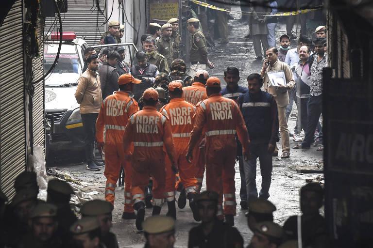 Equipe de bombeiros, vestida de laranja, em meioa área atingida pelo incêndio.