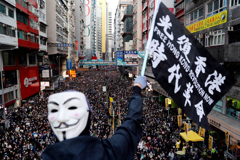 O manifestante está em um lugar alto, acima da multidão. A máscara de Guy Fawkes está de frente para a câmera  e ele balança uma bandeira preta com inscritos brancos no idioma local.