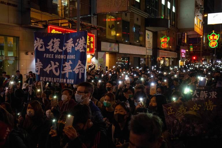 """Homem segura cartaz em que se lê """"Liberdade para Hong Kong, revolução de nossos tempo"""" enquanto pessoas seguram os celulares iluminados durante protesto organizado pela Frente Civil de Direitos Humanos, em Hong Kong"""