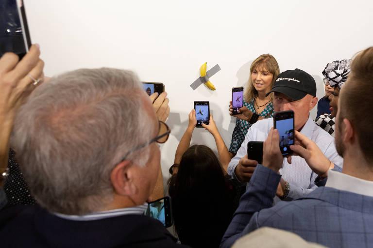 """Pessoas posam ao lado da banana que substituiu a banana comida na instalação """"Comediante"""" do artista Maurizio Cattelan"""