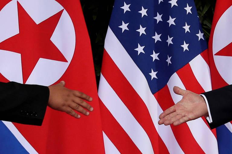 Ao fundo, a bandeira vermelha, azul e branca dos Estados Unidos ao lado da bandeira vermelha e branca da Coreia do Norte, de cada lado da imagem, a mão de um dos dirigentes