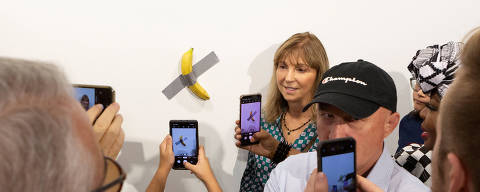 A woman poses for a photo next to a banana attached with duct-tape that replaces the artwork 'Comedian' by the artist Maurizio Cattelan, which was eaten by David Datuna, in Miami Beach, Florida, December 7, 2019.  REUTERS/Eva Marie Uzcategui     TPX IMAGES OF THE DAY ORG XMIT: EM117