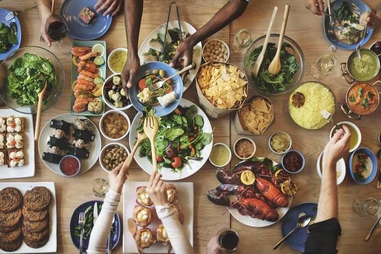 Mesa com comidas e pessoas se servindo