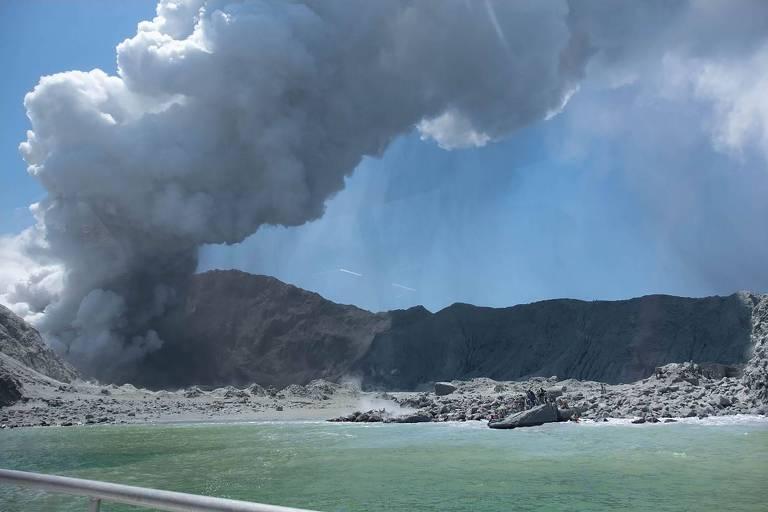 Grande nuvem de fumaça branca se forma após erupção de vulcão. A fumaça está indo em direção a uma cadeia de montanhas, à direita. É possível ver também as águas do mar que cercam a ilha