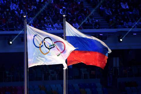 (FILES) This file photograph taken on February 23, 2014, shows the Olympic flag and the Russian flag flying during the Closing Ceremony of the Sochi Winter Olympics at the Fisht Olympic Stadium in Sochi. - The World Anti-Doping Agency (WADA) decided on December 9, 2019, to exclude Russia from the Olympic Games for four years, including Tokyo-2020 and Beijing-2022, to sanction the falsification of test data submitted to the agency, a WADA spokesman said after the Executive Committee meeting in Lausanne (Photo by Andrej ISAKOVIC / AFP) ORG XMIT: PS3309