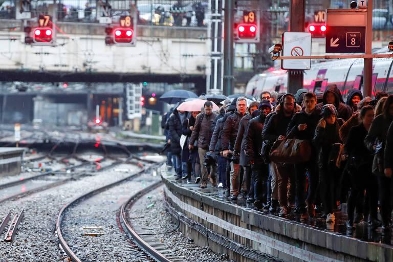 grande número de pessoas está de pé em uma plataforma de trem à espera do veículo