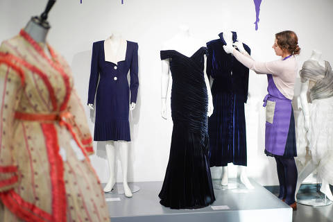 An assistant poses with Britain's Princess Diana's Victor Edelstein midnight-blue velvet evening gown (estimated at £250,000 - £350,000), which was worn by the princess when she danced with actor John Travolta at the White House in 1985. Also pictured is her Katherine Cusack evening gown (estimated at £20,000 -£30,000) and her Catherine Walker dress (estimated £4,000 - £6,000), at Kerry Taylor auctions in London, Britain December 8, 2019. REUTERS/Henry Nicholls ORG XMIT: HTN108