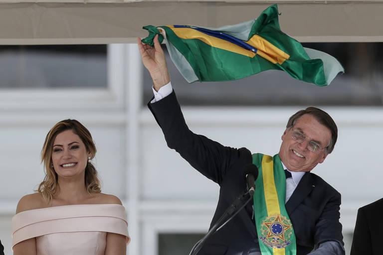 À esquerda, a primeira dama, Michelle Bolsonaro, sorri. À direita, o presidente Jair Bolsonaro usa óculos, está de terno, com a faixa presidencial verde e amarela. Sorri e sacode uma bandeira do Brasil.