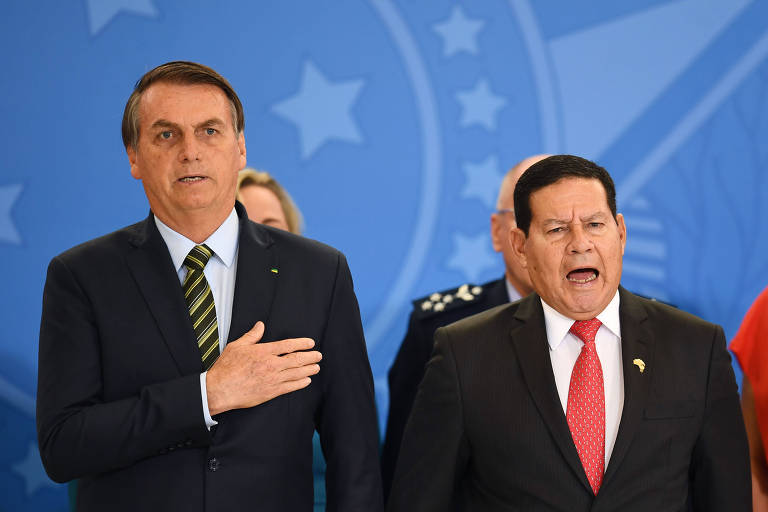 O presidente brasileiro, Jair Bolsonaro, e o vice, Hamilton Mourão, cantam o hino nacional durante cerimônia no Palácio do Planalto nesta segunda (9)